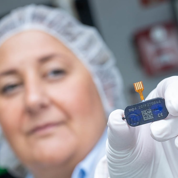 Woman employee with hair covering presenting the mp6 micropump in microfluidics and microtechnology