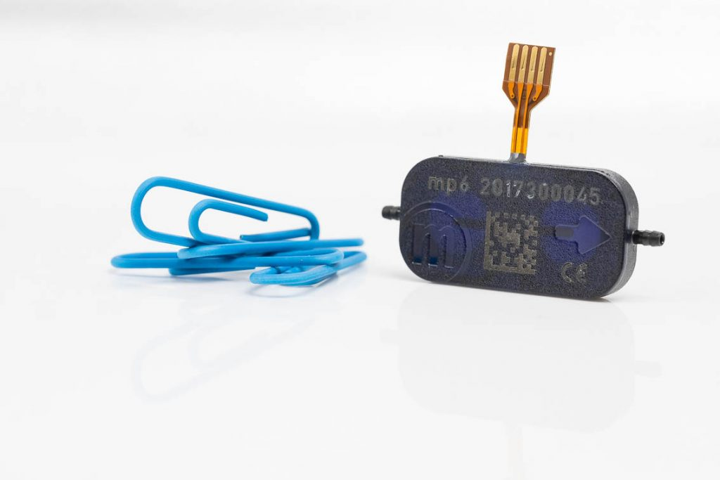 The mp6 micropump in comparison with blue paper clips small pump made by Bartels Mikrotechnik for microfluidics in microtechnology