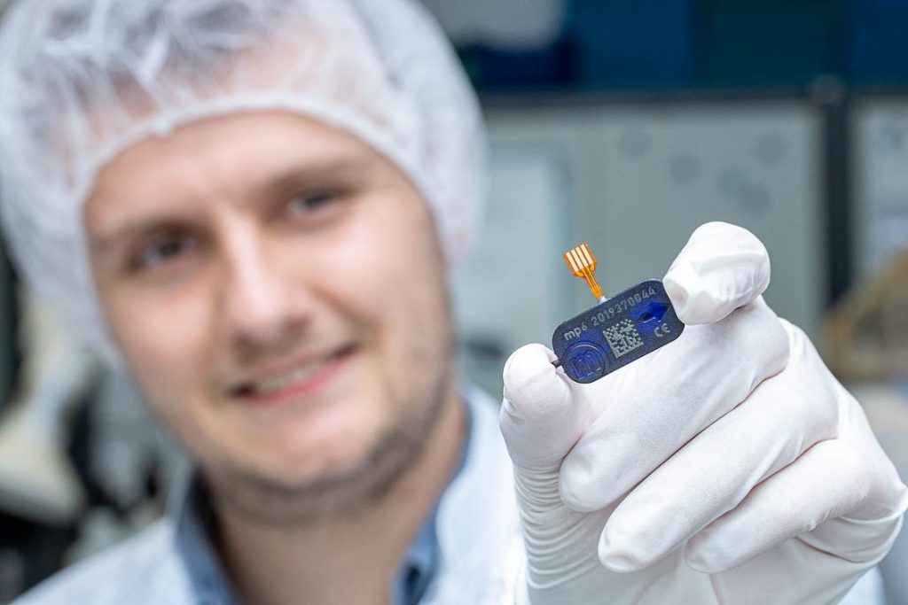 Employee with hair covering presenting the produced mp6 micropump microfluidics and microtechnology