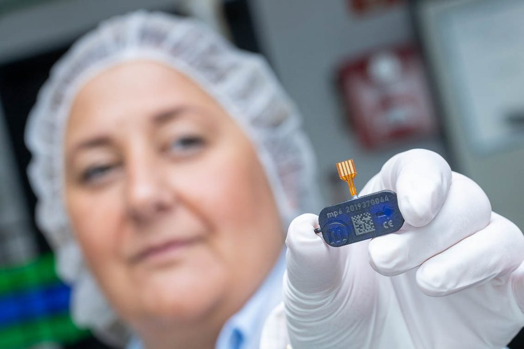 Woman presenting microComponent mp6 micropump for microfluidics from Dortmund (Bartels Mikrotechnik) production with hair covering in a laboratory