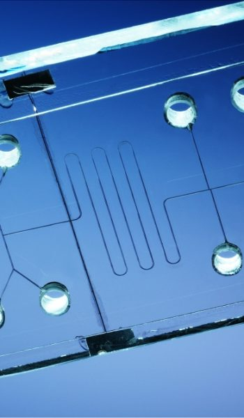 tiny microfluidic channels showing microfluidics and microtechnology with blue background at Bartels Mikrotechnik