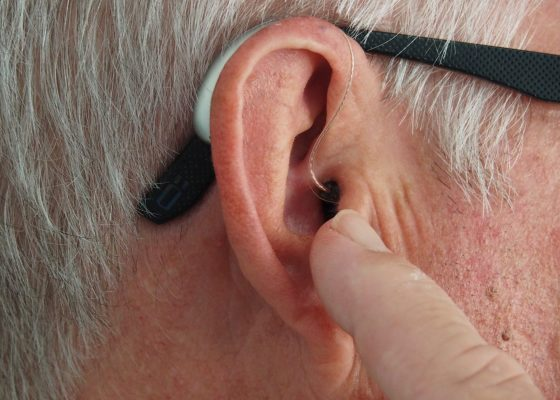 ear of an old man with technological device showing the importance of medical technology nd micropumps for health and care
